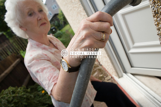 Woman using grab handrails to help her up the steps outside her front door,