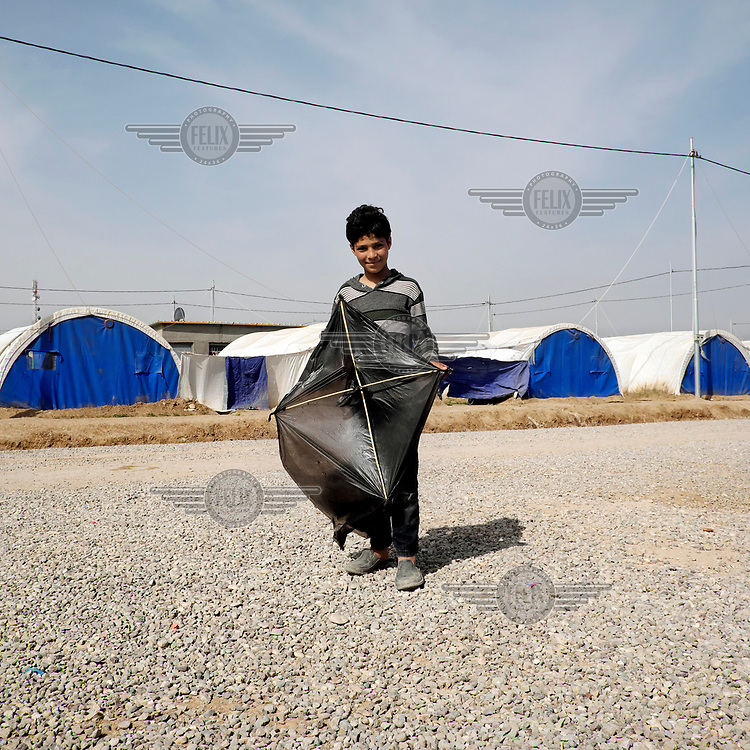 Fahad, a ten year old IDP boy from Mosul, poses with his homemade kite, fashioned out of a plastic bag, at the Al-Khazer IDP camp where he has been with his family for less than two weeks.