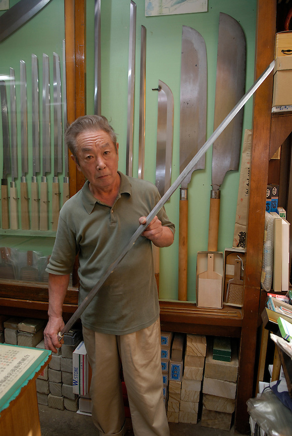 3rd generation knife shop owner Azuma Masahisa holding a tuna knife in his shop. The knife is taller than he is.