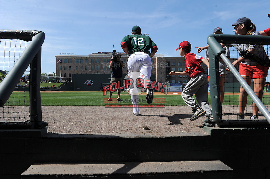 Shortstop Nick Natoli (12) of the Greenville Drive takes the field with a youth baseball fan prior to a game against the West Virginia Power on May 20, 2012, at Fluor Field at the West End in Greenville, South Carolina. Greenville won 6-5. (Tom Priddy/Four Seam Images)