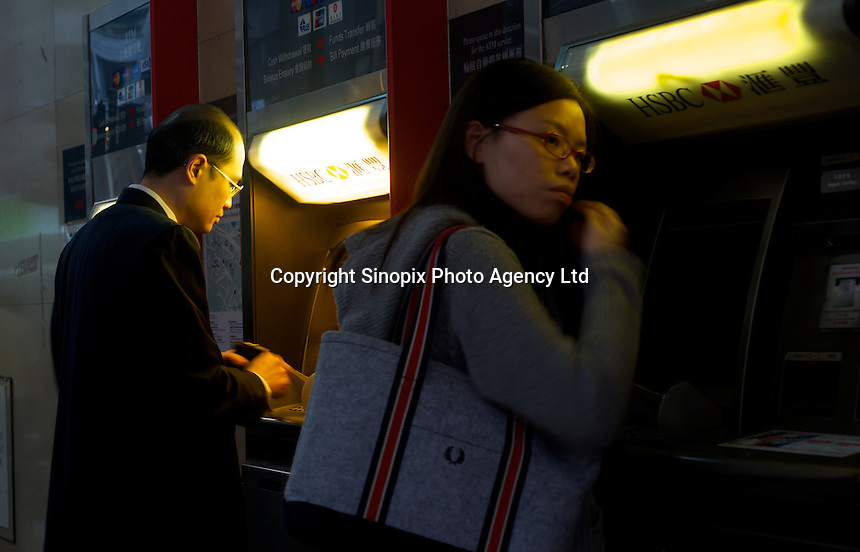 People withdraw cash from a HSBC cash machine (ATM) in Hong Kong. .