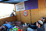 Settlers gather outside their shack, in the unauthorized Israeli outpost of Ramat Migron, West Bank.