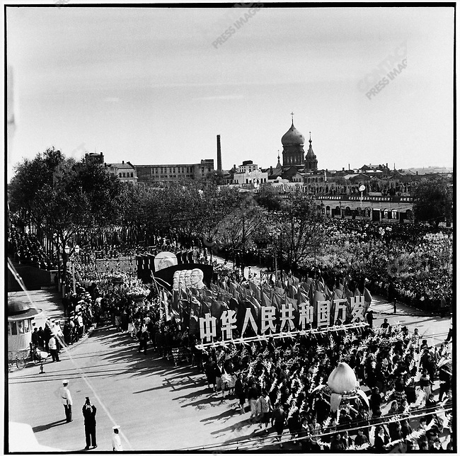 "Marchers in Harbin during the National Day parade carry large wooden characters that read, ""Long live the People's Republic of China,"" and banners with profiles of Marx, Engels, Lenin, and Stalin followed by one of Mao Zedong. The Russian Orthodox cathedral of St. Sophia is visible in the background. 1 October 1963."