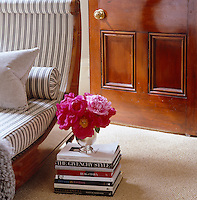 Detail of a vase of pink peonies on a pile of books next to the chaise-longue
