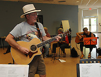 NWA Democrat-Gazette/FLIP PUTTHOFF<br /> FINGERS AT WORK<br /> Guitar teacher Mike Haley leads lessons Tuesday August 18 2015 at the Adult Wellness Center in Rogers. About a dozen students are enrolled in guitar lessons at the center. A picking circle is held at 1 p.m. each Tuesday for any guitar players who wish to play and sing.