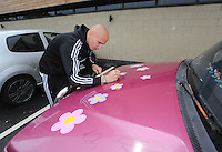 """Pictured: Jonjo Shelvey signs the Suzuki Samurai at the Landore Training Ground. Saturday 10 May 2014<br /> Re: Leigh Evans of Leigh Enterprise Tyres is the new owner of """"the pink Ferrari"""", an old Suzuki Samurai 4x4 car used by Swansea City FC players during the last season."""