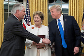 US President Donald J. Trump (R) shakes hands with Rex Tillerson (L) after Tillerson was sworn-in as Secretary of State, as Tillerson's wife Renda St. Clair (C) looks on; in the Oval Office of the White House in Washington, DC, USA, 01 February 2017. Tillerson was confirmed by the Senate, 01 February, in a 56-to-43 vote to become the nation's 69th Secretary of State.<br /> Credit: Michael Reynolds / Pool via CNP
