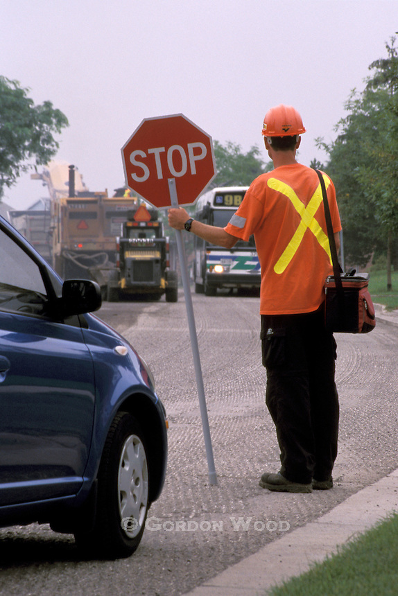 Flagman on Road Resurfacing Project with Stopped Traffic