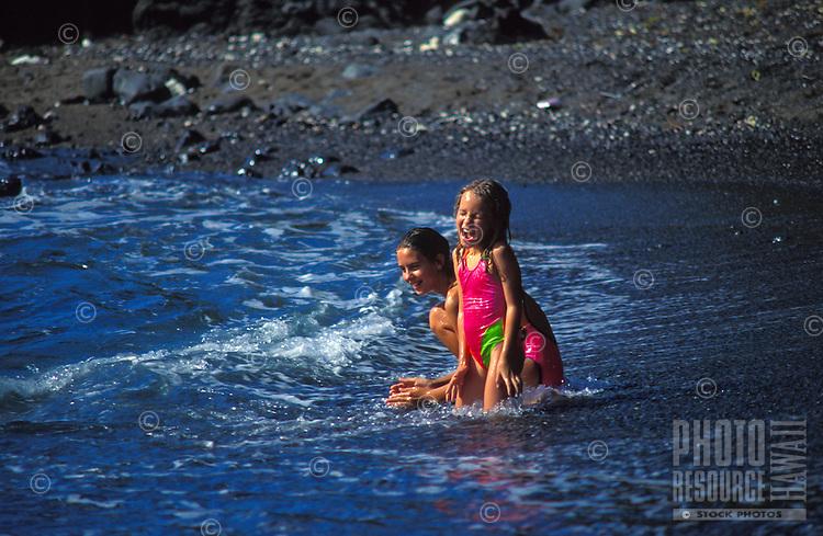 Young girls playing at a black sand beach, Kona, Big Island