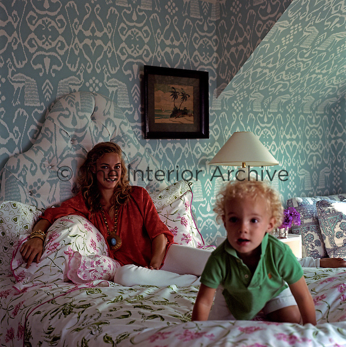 Veronica Beard and her young son on her bed in the master bedroom.