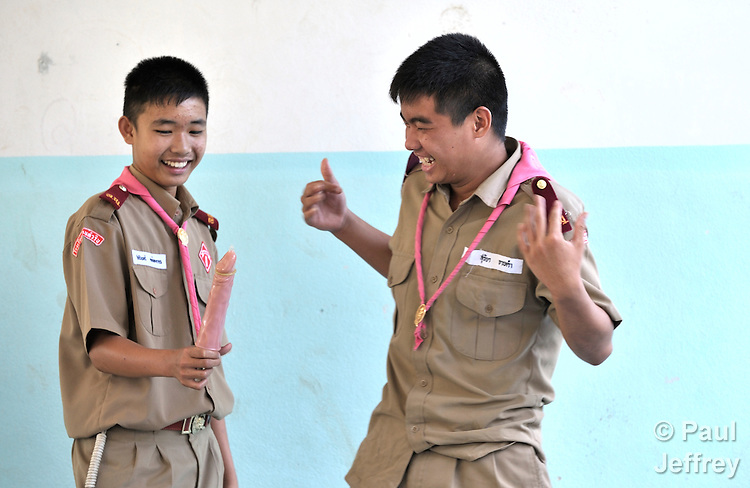 Wearing their scouting uniforms, children in the village of Toong-sa-tok in northern Thailand learn about HIV and AIDS during a session at the temple-supported Banhuarin School. Here two boys standing in front of the class learn how to properly use a condom.