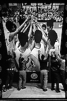 Chinese workers uninstall a picture of Tsinghua University Affiliated Middle School basketball team players celebrating winning last year's China High School Basketball League after a function at Tsinghua University Affiliated Middle School in Beijing, January 2012.