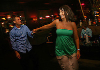 Jennifer Holbrook, of Belleville, Il, leads Josh Ring, of St. Charles, to the dance floor at Home nightclub at the Ameristar Casino in St. Charles, Mo.