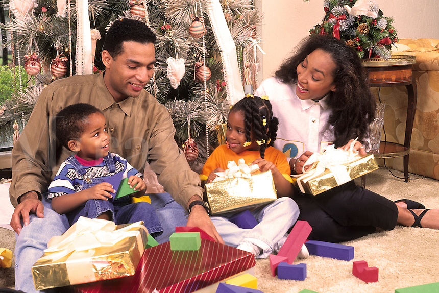 Young family opening Christmas presents.