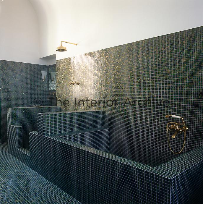 A minimalist tiled bathroom with a shower and bath area.
