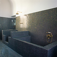 A minimalist tiled bathroom with a shower and bath area.