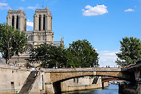 Paris, France. View from a boat on the river Seine. Passing the Notre Dame cathedral and the Petit Pont bridge.