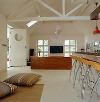 The open-plan kitchen and living area benefits from a high beamed ceiling