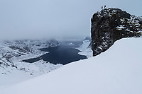 Hiker on rock outcrop overlooking Reinefjord in winter, Moskenesøy, Lofoten Islands, Norway