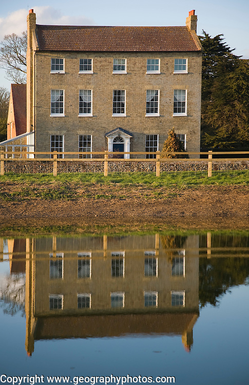 High House Farm farmhouse reflected in water of newly dug pond, Bawdsey, Suffolk, England