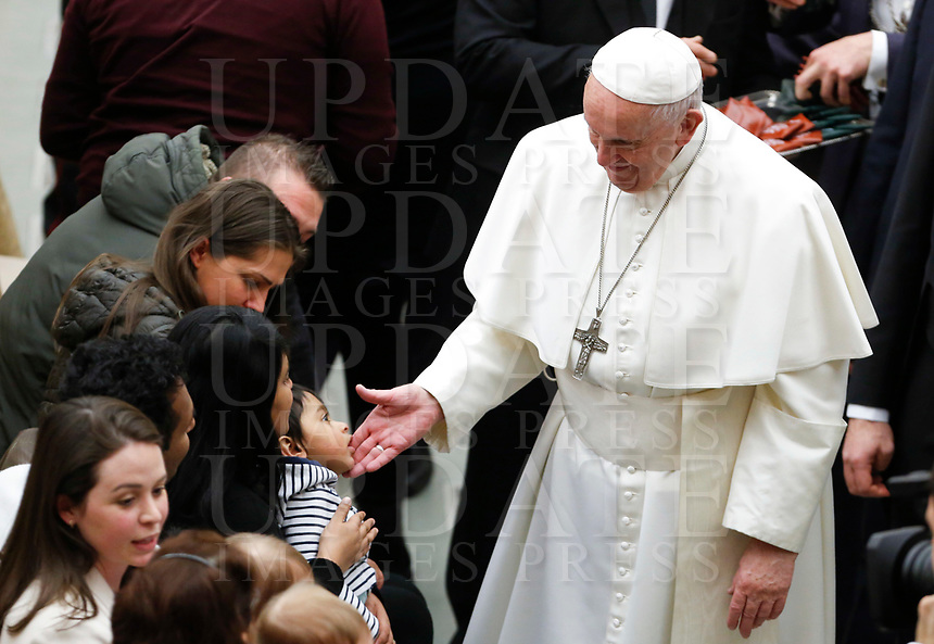 Pope Francis greets a child at the end of his weekly general audience in the Paul VI hall at the Vatican, January 22, 2020.<br />
