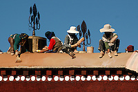 "Workers repair the roof of the Potal Palace. The thirteen-story structure is composed of the White Palace and the Red Palace. Work began on the White Palace in 1645 when the fifth Dalai Lama decided to move his government from the Drepung monastery to the heart of Lhasa high on the terraced slope of the 130-meter ""Red Hill."""