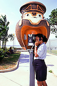 Belem, Brazil. Girl speaking on a phone in a booth in the shape of a Marajoara pot; Ver-o-peso market.