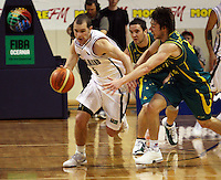 Tall Blacks guard Mike Fitchett drives past Matthew Dellavedova (right) and Adam Gibson during the International basketball match between the NZ Tall Blacks and Australian Boomers at TSB Bank Arena, Wellington, New Zealand on 25 August 2009. Photo: Dave Lintott / lintottphoto.co.nz