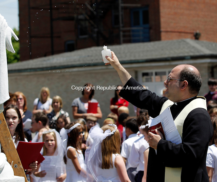 Torrington, CT-17, May 2010-051710CM04  Father John Lavorgna, from St. Peter St. Francis Catholic School in Torrington blesses students and parents, as part of the ceremony Monday morning at the school in Torrington.  The second grade class recently made their First Holy Communion, and were celebrating joined by other grades in the school.  --Christopher Massa Republican-American