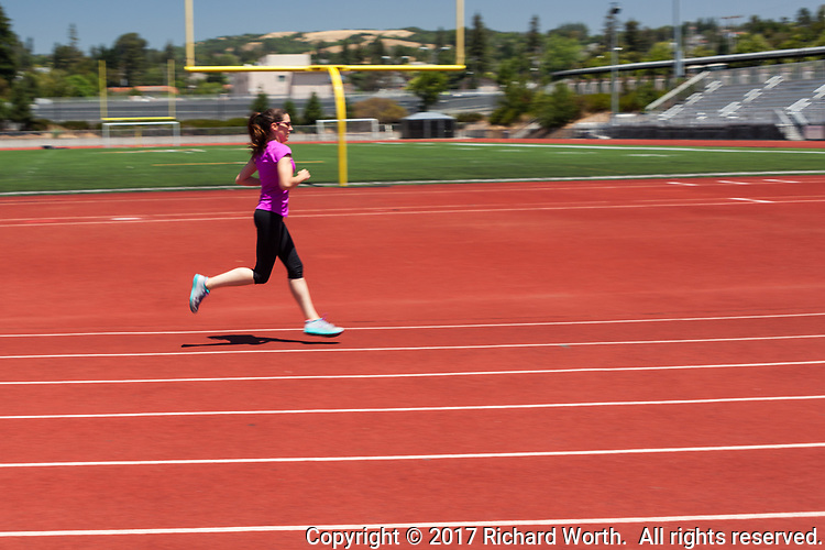 A young woman runner on a track passing a football goalpost in the background, her feet off of the ground.  Motion blur emphasizes action.