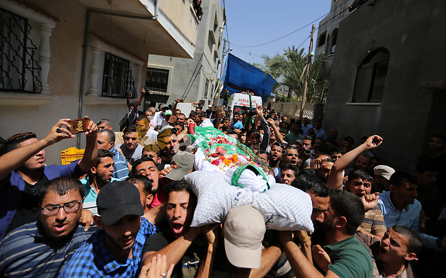Mourners carry the body of Palestinian Mohammed Abu Daqqa, 24, who died of wounds he sustained during clashes with Israeli troops, during his funeral in Khan Younis in the southern of Gaza Strip on June 21, 2018. Photo by Ashraf Amra