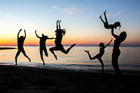 People are silhouetted jumping on a beach on Cape Cod.