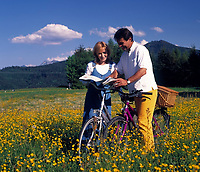 Paar mit Fahrraedern und Landkarte stehen in einer Blumenwiese | couple with bicycles and map standing in a flower meadow