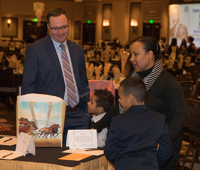 The Markie familey looks at silent auction prizes during the 29th Annual Dr. Martin Luther King, Jr. Dinner Celebration at the Atlantis Casino Resort Spa in Reno, Monday night, Jan. 16, 2017.