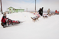 Aliy Zirkle runs up the hill as she arrives at the village checkpoint of Ruby during the 2010 Iditarod
