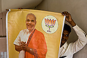 Bhartiya Janta Party (BJP) workers pose with a poster of Gujarat Chief Minister, Narendra Modi at the BJP party office in Ahmedabad, Gujarat, India