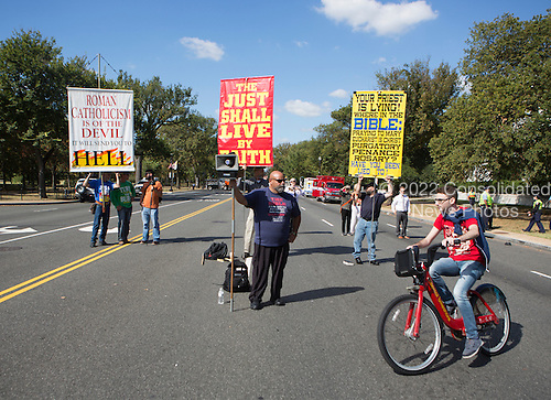 As a bicyclist rides around them, a group of men demonstrate with anti-Catholic slogans near The White House in Washington DC where United States President Barack Obama hosted an Official State Welcome ceremony for Pope Francis on Wednesday, September 23, 2015.  <br /> Credit: Chris Kleponis / CNP