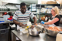 Rider Semedo, 27, of Cape Verde, (left) and Doris Mateljuk, 21, prepare meat for lobster rolls for the dinner service at Home Port restaurant in Chilmark/Menemsha, Martha's Vineyard, Massachusetts, USA. It is Semedo's first season working as a temporary worker on Martha's Vineyard. Mateljuk has a J1 visa for foreign students to temporarily work in the US. It's her second year working at the restaurant and she will return to Croatia in October. She studies occupational therapy. Home Port did not receive any H2B temporary foreign worker visas this year and has had difficulty filling all positions in the kitchen. On the day of this picture, one scheduled worker did not come to work and the restaurant could not find a backup to fill in. The restaurant has also quit serving lunch as a result of difficulty in finding workers.