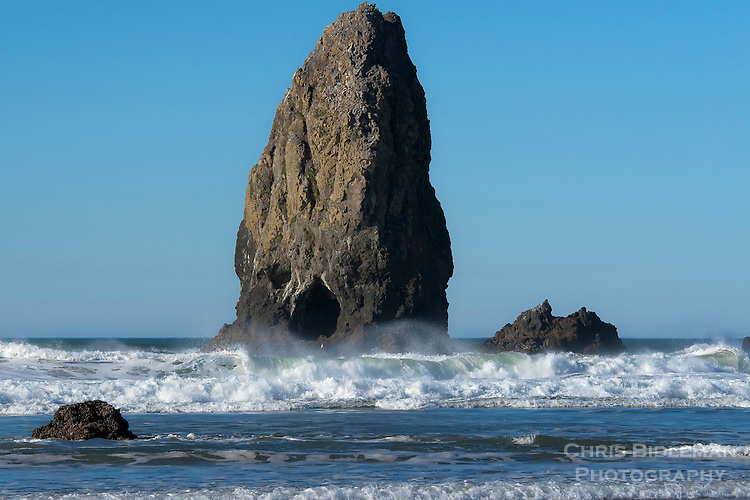 The Needles in Cannon Beach near Haystack Rock on a blue sky day with waves rolling in