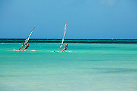 Windsurfing along the beaches of Aruba. Aruba remains a popular tourist destination, with international planes and cruise ships arriving daily. Aruba, part of the Lesser Antilles, is famous for its white sand beaches, blue/green waters and mild climate.