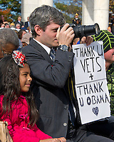 A spectator holds a sign as he takes photos during United States President Barack Obama's remarks in the Memorial Amphitheater at Arlington National Cemetery in Arlington, Virginia after laying a wreath at the Tomb of the Unknown Soldier on Veteran's Day, Friday, November 11, 2016.<br /> Credit: Ron Sachs / Pool via CNP /MediaPunch