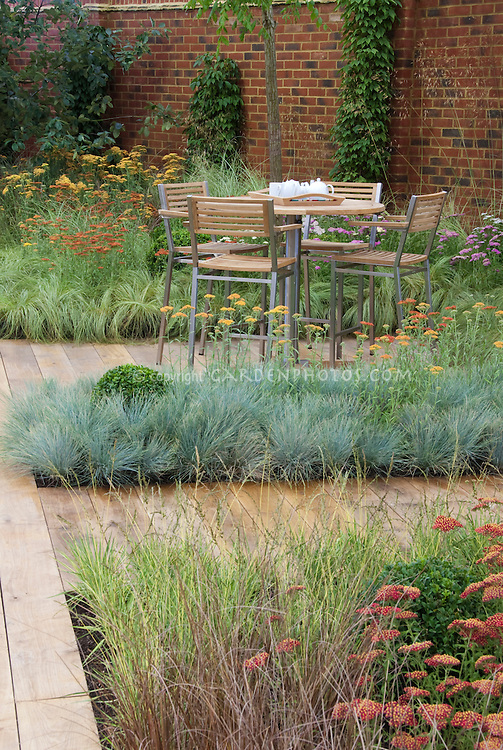 Home and garden with patio furniture table and chairs, wooden deck plantings of Achillea, Festuca and other ornamental grasses for xeriscaping dry landscape water-wise plants, brick wall, climbing vines for vertical interest