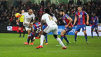 A shot by Andre Ayew of Swansea (L) deflects off Pape Souare of Crystal Palace during the Barclays Premier League match between Swansea City and Crystal Palace at the Liberty Stadium, Swansea on February 06 2016