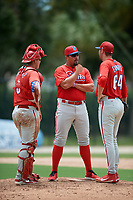 GCL Phillies West pitching coach Matt Hockenberry (33) talks with relief pitcher Ethan Evanko (64) and catcher Abraham Gutierrez (3) during a game against the GCL Blue Jays on August 7, 2018 at Bobby Mattick Complex in Dunedin, Florida.  GCL Blue Jays defeated GCL Phillies West 11-5.  (Mike Janes/Four Seam Images)