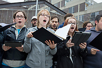 """A protest choir calling itself """"Vocal Opposition"""" warms up before the March for Science demonstration in Harvard University's Science Center Plaza in Cambridge, Massachusetts, on Sat., April 22, 2017. The group sang protest songs throughout the day, including at the Harvard, MIT, and Boston Common rallies. Many of the songs included humorous references to science and protest."""