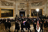 Cabinet members of the late former President George H.W. Bush walk past the casket as he lies in state inside the Rotunda of the US Capitol, December 3, 2018 in Washington, DC. - The body of the late former President George H.W. Bush travelled from Houston to Washington, where he will lie in state at the US Capitol through Wednesday morning. Bush, who died on November 30, will return to Houston for his funeral on Thursday. (Photo by Brendan Smialowski / AFP)