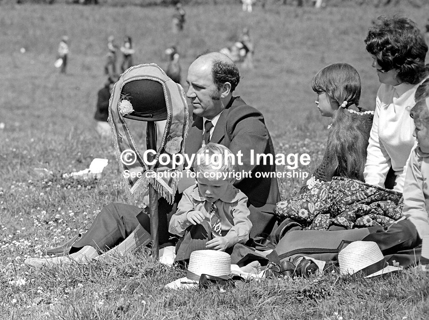 Orangeman relaxes with his family at The Field at Edenderry after the long march from Belfast. His rolled umbrella spiked into the ground provides a temporary stand for his bowler hat and Orange collarette. Twelfth, 12th July 1974. 197407120383a<br /> <br /> Copyright Image from Victor Patterson, 54 Dorchester Park, Belfast, UK, BT9 6RJ<br /> <br /> Tel: +44 28 9066 1296<br /> Mob: +44 7802 353836<br /> Voicemail +44 20 8816 7153<br /> Email: victorpatterson@me.com<br /> Email: victorpatterson@gmail.com<br /> <br /> IMPORTANT: My Terms and Conditions of Business are at www.victorpatterson.com