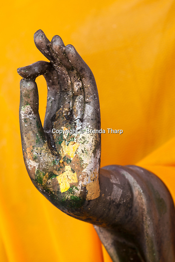 Classic hand symbol of a statue of Buddha receives gold-leaf from devotees who enter the temple. Thailand.