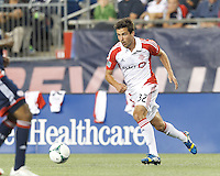 Toronto FC forward Andrew Wiedeman (32) brings the ball forward.  In a Major League Soccer (MLS) match, Toronto FC (white/red) defeated the New England Revolution (blue), 1-0, at Gillette Stadium on August 4, 2013.