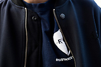 Tyler Rodgers, 30, a Master of Public Policy grad student at Harvard, wears a Resistance School shirt under his jacket while directing attendees to the lecture space before a session of Resistance School at Harvard University's John F. Kennedy School of Government, on Thurs., April 27, 2017.